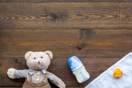 Handmade toys for newborn baby. Teddy bear. Feeding bottle with milk and dummy. Wooden background top view mockup