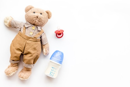 Handmade toys for newborn baby. Teddy bear. Feeding bottle with milk and dummy. White background top view mockup