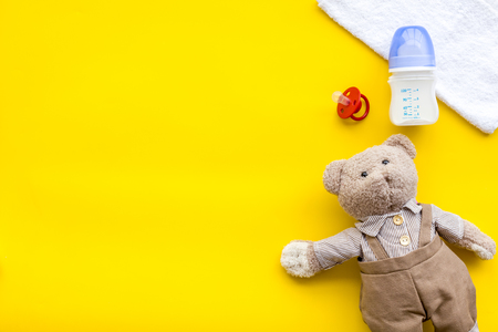 Handmade toys for newborn baby. Teddy bear. Feeding bottle with milk and dummy. Yellow background top view mockup Imagens