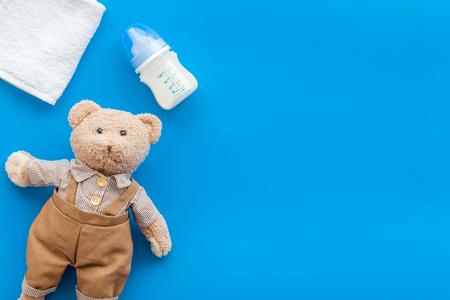 Handmade toys for newborn baby. Teddy bear. Feeding bottle with milk. Blue background top view mockup