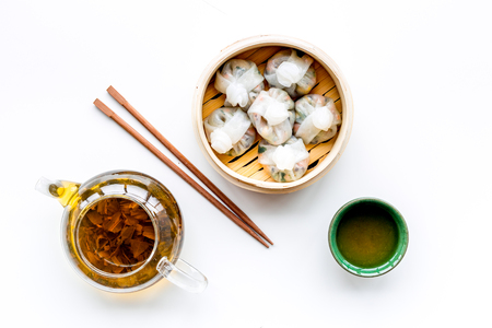 Dim sums with sticks and herbal tea in Chinese restaurant on white background top view