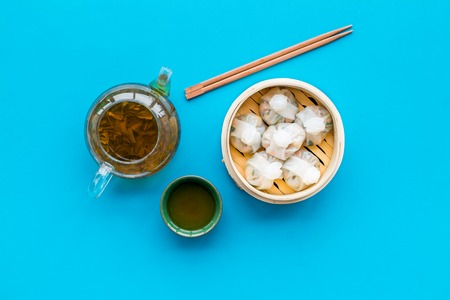 Chinese steamed dumplings Dim Sum in bamboo steamer with tea on blue background top view