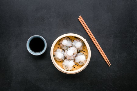 Chinese food set with dim sum, sticks on black background top view copy space