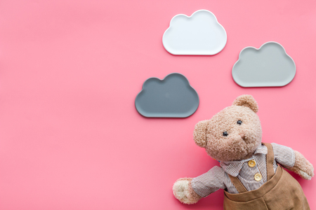 Toys for newborn baby set with teddy bear and clouds on pink background flat lay space for text