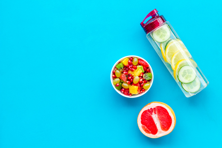 Diet rich in fruits. Slimming diet. Fruit salad near fruit lemon and cucumber water on blue background top view space for text Stock Photo