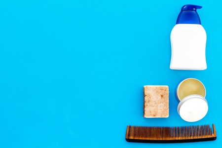 Male care set for barbershop with shampoo bottle and comb on light blue background top view mock-up