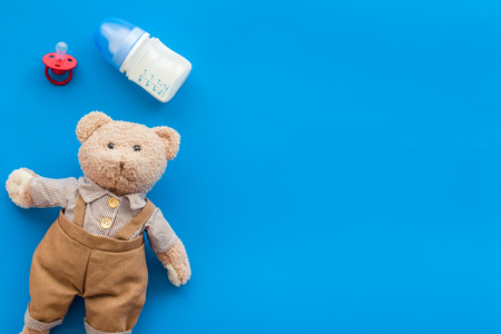 Baby care with craft toys for newborn. Teddy bear. Blue background top view copy space Stock Photo