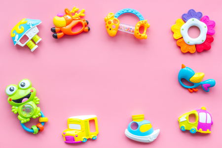 Toys for newborn baby set with plastic rattle frame on pink background flat lay space for text Foto de archivo - 114655030