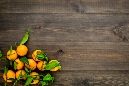 Winter fruits for New Year and Christmas. Tangerines on wooden background top view mock-up