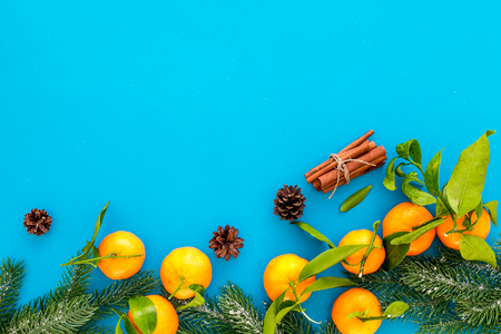 Pile of tangerines, fir tree and cinnamon for New Year and Christmas celebration on blue background top view mock up Stock Photo