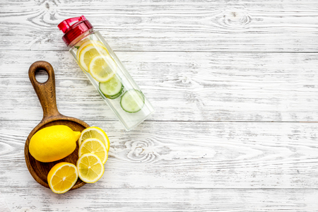 Detox infused water with slices of lemon and cucumber in bottle on white wooden background top view.