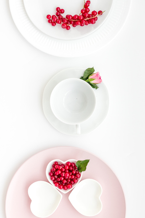 Set-up table with plates, wineberry and flower on white background top view