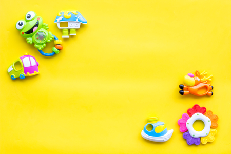 Baby care with craft toys for newborn. Rattle. Yellow background top view copy space Foto de archivo - 114765738
