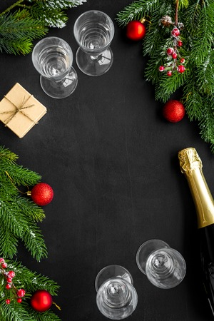 Spruce, champagne bottle and glasses for Christmas celebration on black background top view mockup