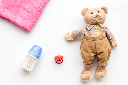 Toys for newborn baby set with teddy bear and milk in bottle on white background flat lay Stockfoto