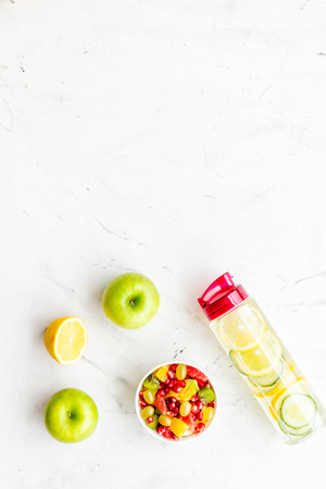 Diet rich in fruits. Slimming diet. Fruit salad near fruit lemon and cucumber water on white background top view space for text Stock Photo