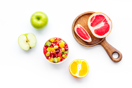 Healthy diet concept. Fruit salad near fresh fruits on white background top view