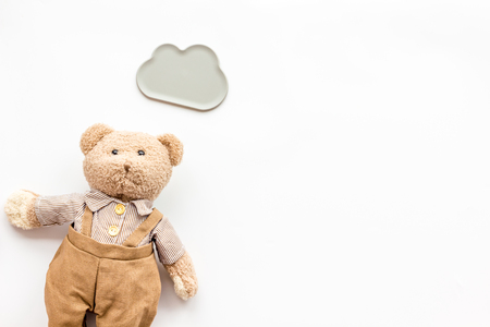 Toys for newborn baby set with teddy bear and clouds on white background flat lay space for text