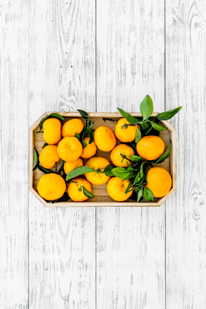 Winter fruits for New Year and Christmas. Tangerines on white wooden background top view mock-up