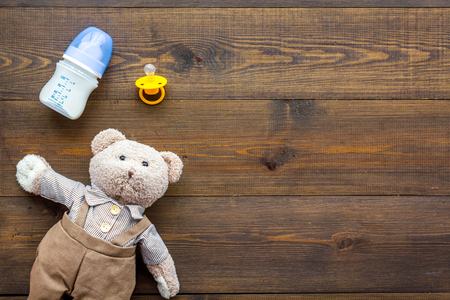 Craft toys for kids. Handmade teddy bear, dummy and baby bottle with milk. Wooden background top view mock up