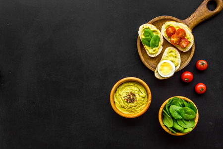Make avocado bruschettas. Toasts with vegetables and guacamole on black background top view space for text Foto de archivo - 114891667