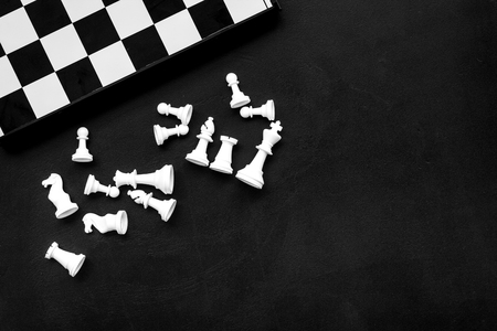 Symbol of competition. Chess board and chess figures on black background top view space for text