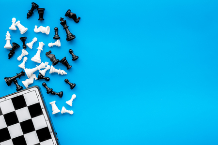 Symbol of competition. Chess board and chess figures on blue background top view copy space