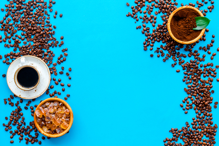 Brown roasted coffee beans scattered on blue table background and cup of Americano top view mockup Stock Photo