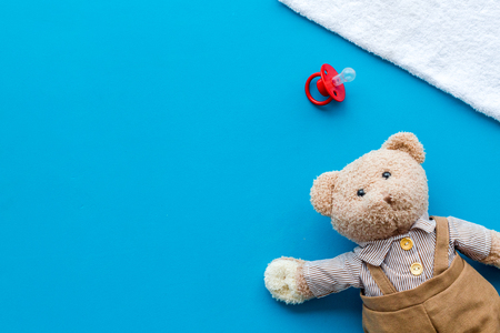 Baby care with craft toys for newborn. Teddy bear. Blue desk background top view copy space