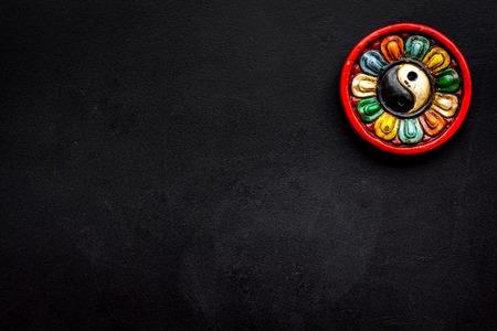 Buddhist symbol. Yin Yang symbol on black background top view.