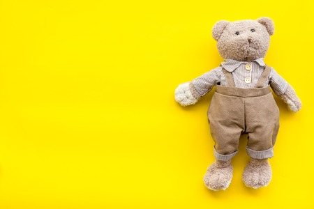 Craft toys for kids. Handmade teddy bear. Yellow desk background top view mock up Stockfoto