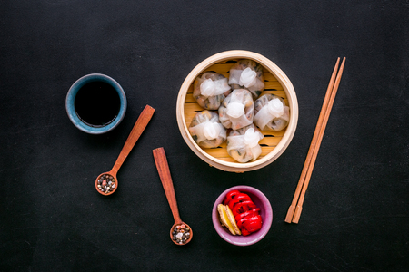 Dinner in Chinese restaurant with dim sum, sticks and tea on black table background top view