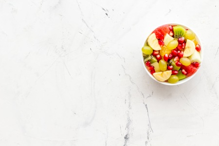 Fruit diet concept. Fruit salad with apple, kiwi and pomegranate in bowl on white stone background top view. Stock Photo