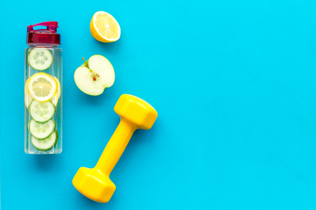 Healthy fruit water for sport, fitness. Bottle of water with lemon and cucumber near sport equipment on blue background top view. 版權商用圖片