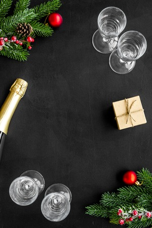 New year and Christmas party with spruce branch, champagne bottle and glasses on black background top view space for text