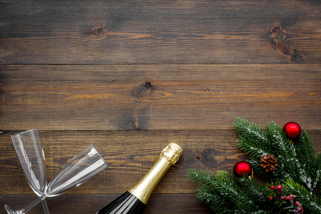 New Year celebration with spruce branch, champagne and glasses on wooden table background top view mock up