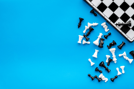 Symbol of competition. Chess board and chess figures on blue background top view. Stock Photo
