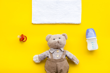 Toys for newborn baby set with teddy bear and milk in bottle on yellow desk background flat lay space for text