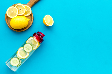 Make detox fruit water. Slices of lemon and cucumber in bottle on blue background top view. Stock Photo