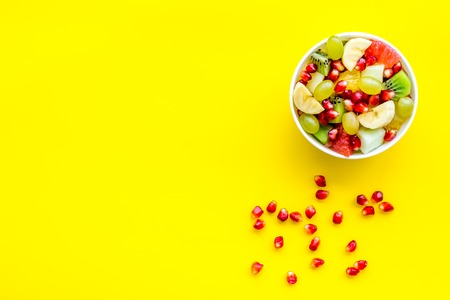 Light healthy breakfast or appetizer. Fruit salad with apple, kiwi and pomegranate in bowl on yellow background top view. Stock Photo