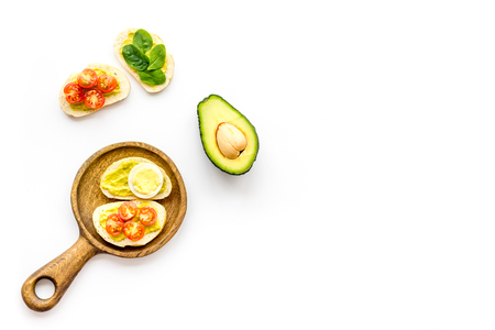 Make avocado bruschettas. Toasts with vegetables and guacamole on white background top view. Foto de archivo - 115150599