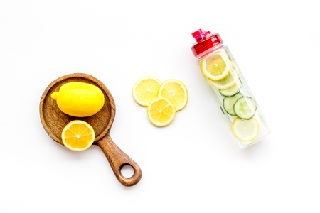 Detox infused water with slices of lemon and cucumber in bottle on white background top view copy space