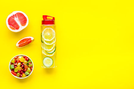 Diet rich in fruits. Slimming diet. Fruit salad near fruit lemon and cucumber water on yellow background top view space for text