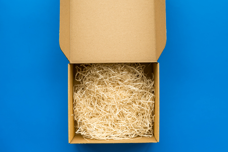 E-commerce. Delivery of goods that was purchased online. Empty cardboard box with cut paper on blue background top view space for text Stock fotó