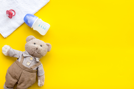 Craft toys for kids. Handmade teddy bear, dummy and baby bottle with milk. Yellow background top view mock up