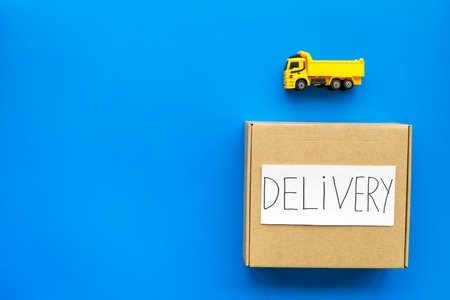 Cargo delivery concept. Cardboard box with written word delivery near toy truck on blue background top view copy space
