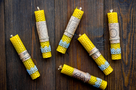 Buddhism. Candles with Yantras and mantras in Sanskrit on dark wooden background top view