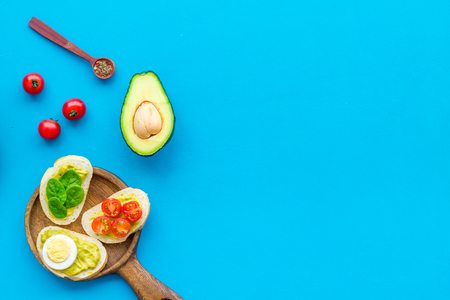 Make avocado bruschettas. Toasts with vegetables and guacamole on blue background top view copy space Foto de archivo - 115239830