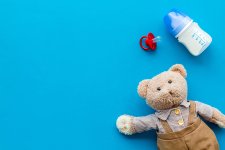 Toys for newborn baby set with teddy bear and milk in bottle on blue background flat lay space for text Фото со стока