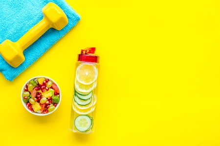 Healthy lifestyle, healthy habits. Detox water, fruit salad, sport equipment dumbbells on yellow background top view space for text 版權商用圖片